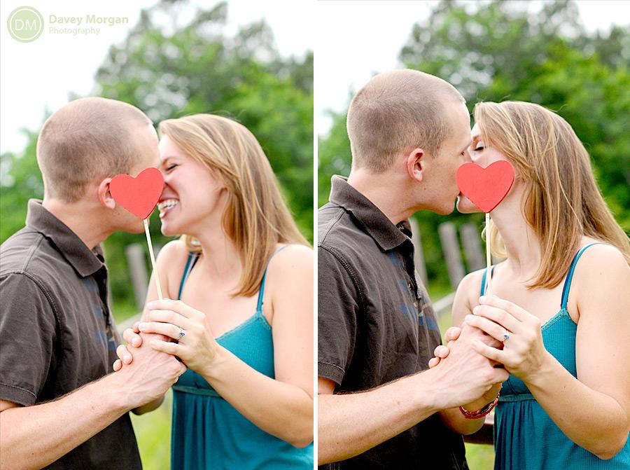 Couple kissing behind photo booth hearts | Davey Morgan Photography
