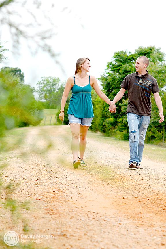 Engaged couple walking down dirt road | Davey Morgan Photography