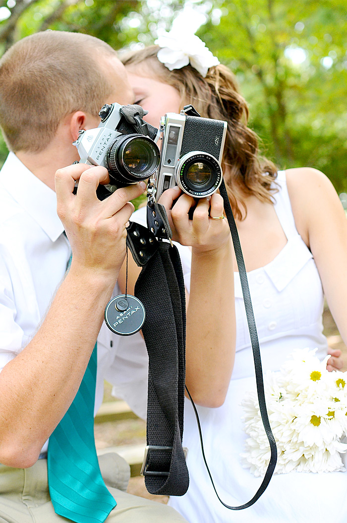 bride and groom kissing behind vintage film cameras | Davey Morgan Photography